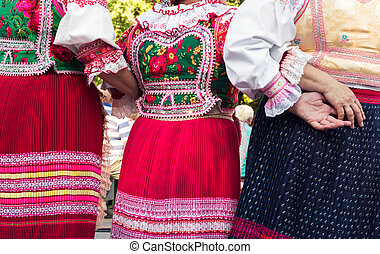 Anonymous senior female friends in folklore costumes