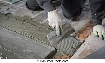 Anonymous site worker applying cement on floor and laying...