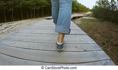Anonymous traveler walking on wooden path in forest