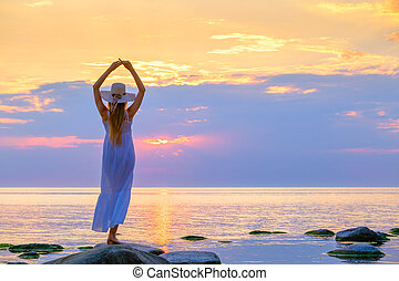 Anonymous woman in sunhat standing near sea