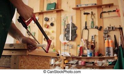 Anonymous woman sawing stick - Crop woman using saw to split...