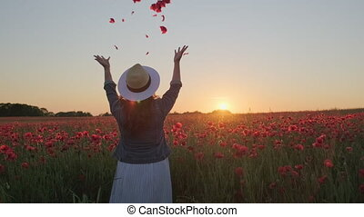 Pan right view of unrecognizable female throwing flower petals in air while having fun in poppy field during sundown