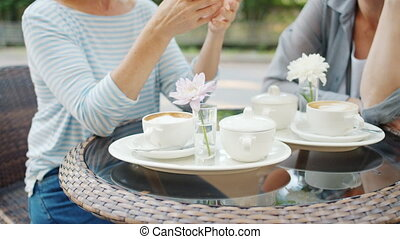 Anonymous women sitting at table in street cafe gesturing,...