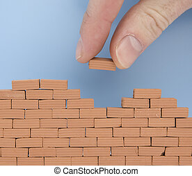 hand putting a brick on a wall