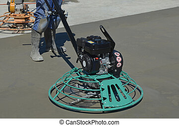 another concrete pour - A builder uses a mechanical float to...