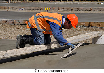 another concrete pour - A builder uses a wooden trowel to...