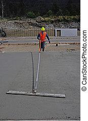 another concrete pour - A builder uses a long handled trowel...
