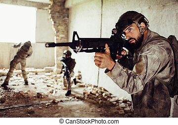Another picture of brave soldiers. Bearded man is standing in front with rifle. Second guy is standing in the middle of room on one knee and looking straight. Third one is near window.