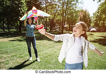 Another picture of girl playing with kite with her mom. Girl is standing in a front and pulling thread from kite. Woman is holding kite and trying to launch it.