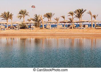 ansicht, von, der, lagune, meer, sandstrand, palmen, und, a, fallschirm, an, sonnenuntergang