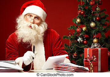 Answering letters - Portrait of Santa Claus looking at...