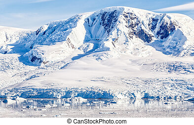 Antarctic mountain covered with snow glacier and waters with icebergs, Neco bay, Antarctica