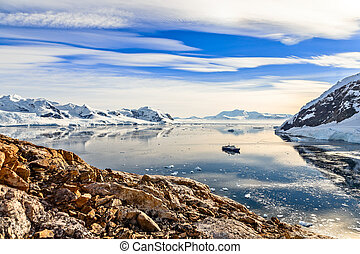 Antarctic mountain landscape with cruise ship standing still in