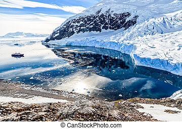 Antarctic mountain landscape with cruise ship standing still on