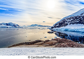 Antarctic mountain landscape with cruise ship standing still on the surface of Neco bay, Antarctica