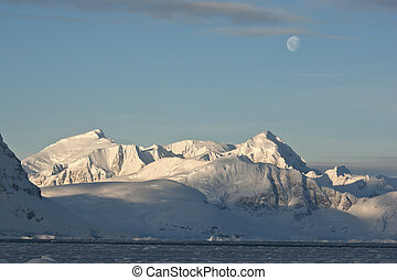 Antarctic mountains under the moonlight on a day.