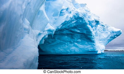 Huge blue iceberg with natural cave inside