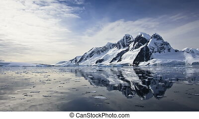 Antarctic Nature: snow-capped mountains reflected in ocean