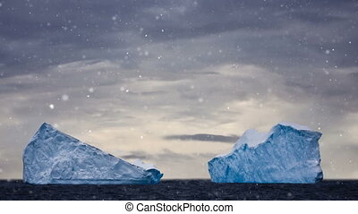 Antarctic Nature: two big icebergs floating in open ocean -...