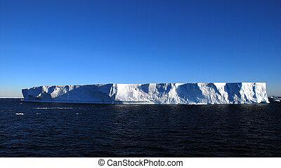 antarctic tabular iceberg floating in the ocean, full sun
