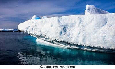 Huge white frozen iceberg float in open ocean - Antarctica....