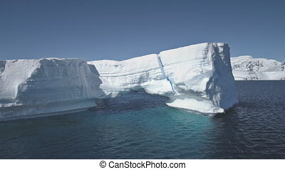 Antarctica iceberg aerial zoom out view drone flight. Overview snow ice mountains archipelago among polar winter ocean. Harsh environment. 4k