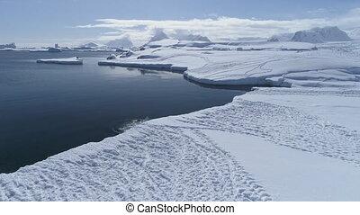 Antarctica landscape, penguins starting to swim.