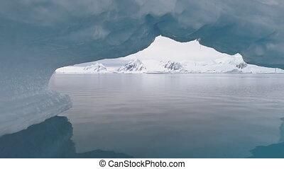 Antarctica shot through iceberg arch. - Antarctica Shot...