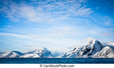 Antarctica: snow-capped mountain range against blue sky -...