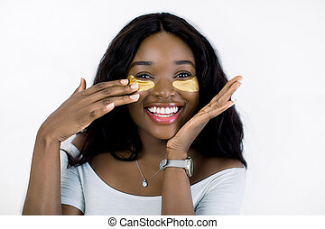 Anti aging eye skin treatment. Smiling attractive African American woman applies medical golden patches under eyes, while standing against white background. Beauty portrait, close up
