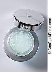 Anti-aging serum in opened glass jar.