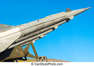 anti aircraft rockets of a surface-to-air missile system are aimed at the blue sky, close up
