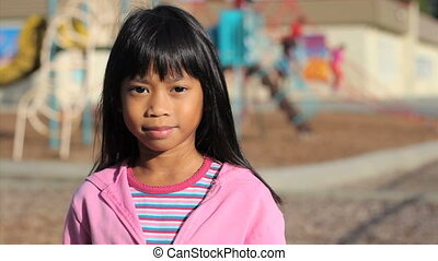 Anti-Bullying Message - A cute Asian girl holds up a small...