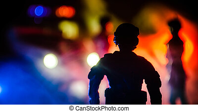 Anti-riot police give signal to be ready. Government power concept. Police in action. Smoke on a dark background with lights. Blue red flashing sirens.