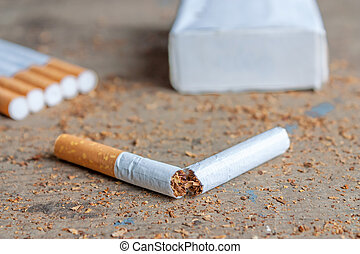 Anti-smoking background with broken cigarette on wooden surface