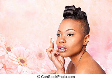 Face of beautiful woman applying facial moisturizer exfoliating anti wrinkle aging cream under eyes, skincare concept, on pink flowers.