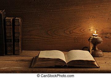 antigas, livro, ligado, um, tabela madeira, por, luz vela