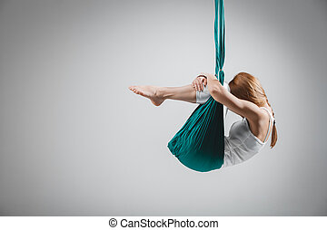 Antigravity Yoga - Stock Image - An adult woman practices...