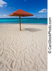 Shelter on white sand beach by turquoise waters on tropical island