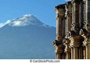 Antigua, Guatemala - Cloud-capped volcano above old houses...