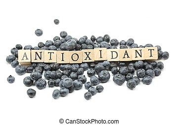 Blueberries on a white background with Antioxidant spelled out in wooden blocks.