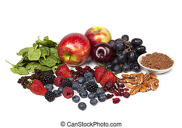 Foods rich in antioxidants, isolated on white. Includes spinach, raisins, apples, plums, red grapes, cocoa powder, pecans, cranberries, strawberries, blueberries, raspberries and blackberries.