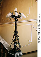 Antique antique lamp on the stair railings against the patterned wall.