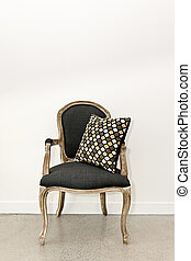 Antique armchair furniture with cushion against white wall