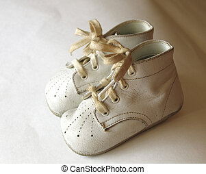antique baby shoes on white background
