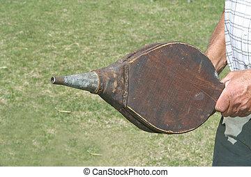 antique bellows - A man holds antique bellows.