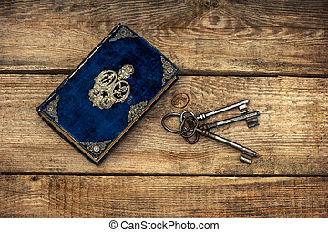 antique book and old keys over rustic wooden background