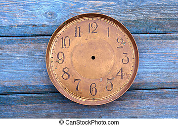 Antique brass clock face on blue wooden background