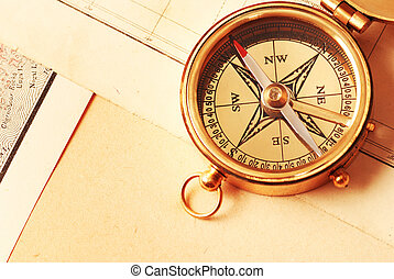 Antique brass compass over old map background...