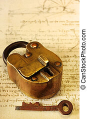 Antique brass padlock and key, on page of Leonardo Da Vinci's writings. The padlock is 19th Century vintage, from India.